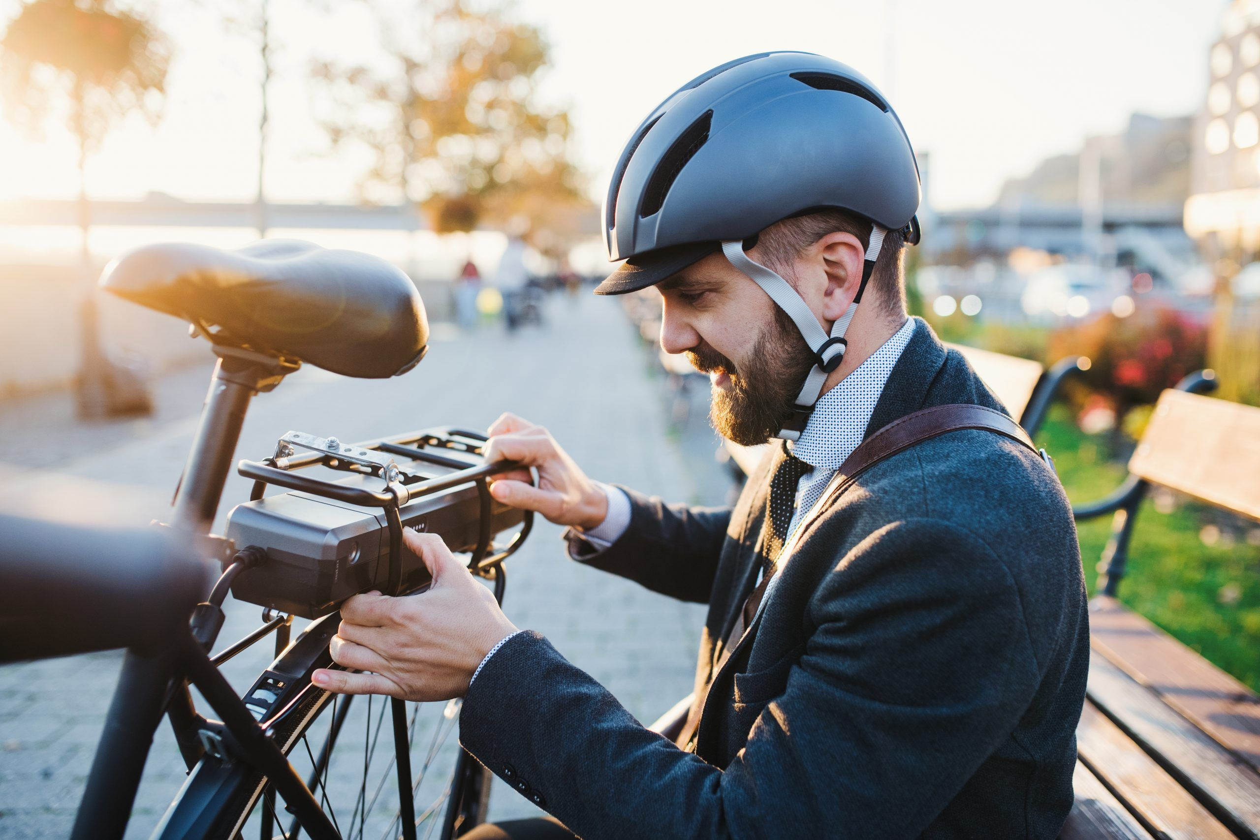 Commuter in suit and cycling helmet checking battery on electric bicycle
